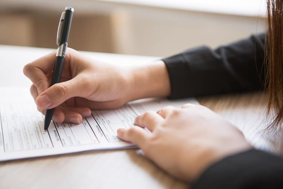 woman signing forms for divorce